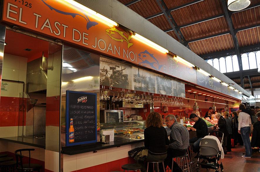 En el Mercado de la Llibertat de Barcelona se encuentra el Tast de Joan Noi (John Boy) donde se pueden degustar platos de marisco y pescado frescos